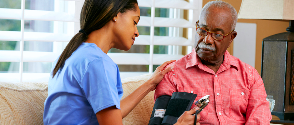 caregiver checking blood pressure to an elderly